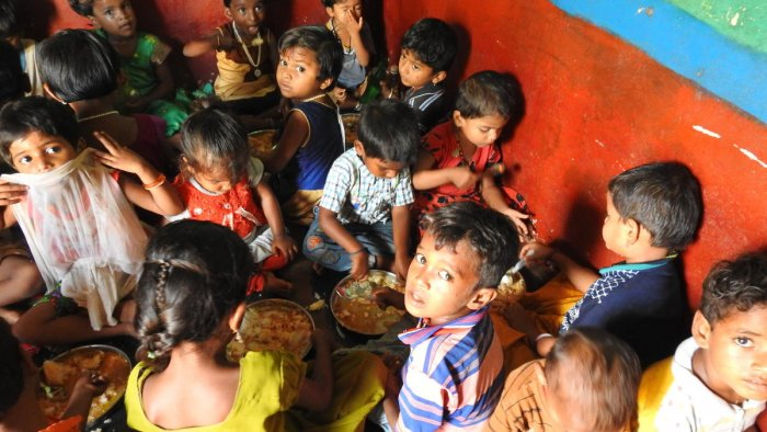 Two kids had to eat from the same plate at an Anganwadi due to the shortage of plates. (DH Photo/Anitha Pailoor)