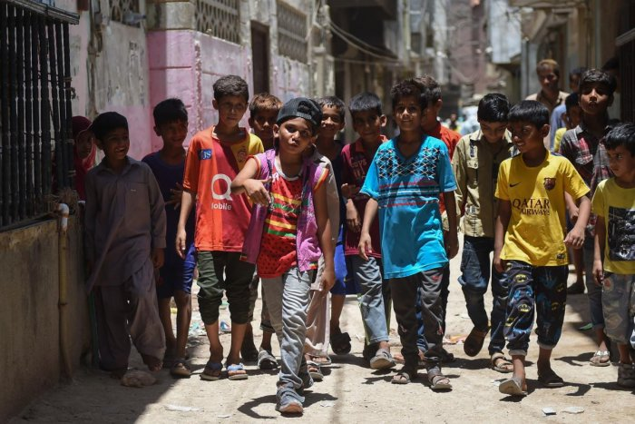In this picture taken on May 19, 2019, eight-year-old rapper Waqas Baloch (C) performs in Lyari, one of Pakistan's most dangerous neighbourhoods, in Karachi. (Photo by RIZWAN TABASSUM / AFP)