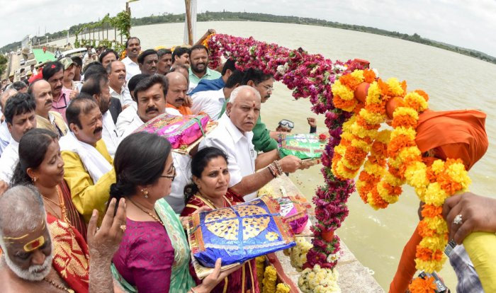 Chief Minister B S Yediyurappa offers bagina to River Cauvery at KRS dam in Mandya district on Thursday. MP A Sumalatha, Mysuru Mayor Pushpalatha Jagannath, ex-MLA Narayan Gowda, MLA Ravindra Srikantaiah and Revenue Minister R Ashoka are seen.