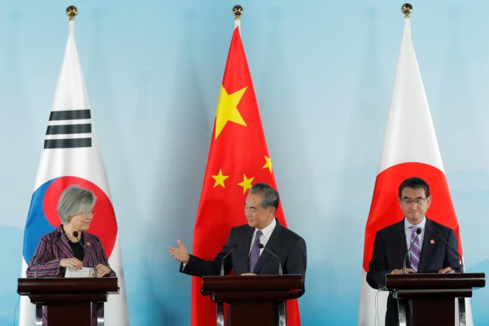Chinese Foreign Minister Wang Yi (C) gestures to South Korean Foreign Minister Kang Kyung-wha (L) beside Japanese Foreign Minister Taro Kono (R) during a press conference after the ninth trilateral foreign ministers' meeting among China, South Korea and Japan at Gubei Town in Beijing, China, 21 August 2019. REUTERS