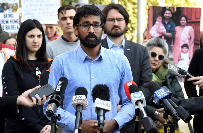 Tamil Refugee Council spokesperson Aran Mylvaganam (C) speaks to the media as protesters hold up placards and photos outside the Federal Court in Melbourne on August 30, 2019. Photo/ AFP
