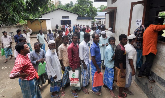 People stand in a queue to check their names on the final list of the National Register of Citizens (NRC) outside a Gaon Panchayat office in Pavakati village, Morigoan. (PTI Photo)