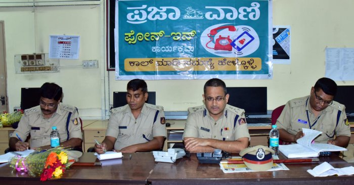 Commissioner of Police Dr P S Harsha receives a call during the phone-in programme organised by Prajavani at DH-PV editorial office in Balmatta on Friday. DH PHOTO