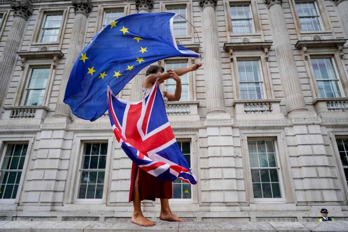 An anti-Brexit demonstrator whirls an EU and Union Flag during a demonstration against the British government's move to suspend parliament in the final weeks before Brexit outside Downing Street in London on August 31, 2019. (Photo by AFP)