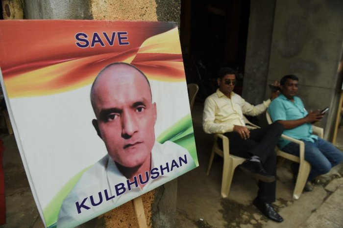 Indian residents sit next to a placard with the picture of Kulbhushan Jadhav, an Indian national convicted of spying in Pakistan, in the neighbourhood where he grew up, in Mumbai on July 17, 2019. (Photo by AFP)