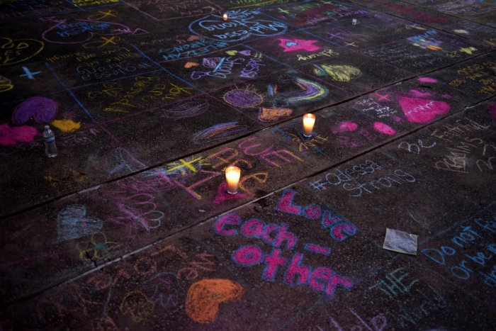 Messages written in sidewalk chalk are seen as people gather for a vigil following Saturday's shooting in Odessa, Texas, U.S. September 1, 2019. (REUTERS)