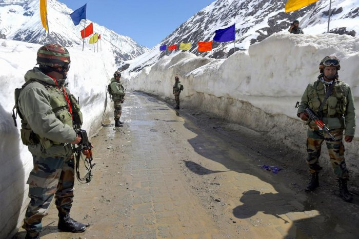 Army soldiers stand guard at snow-bound Zojila Pass, situated at a height of 11,516 feet, on its way to frontier region of Ladakh. (PTI Photo)