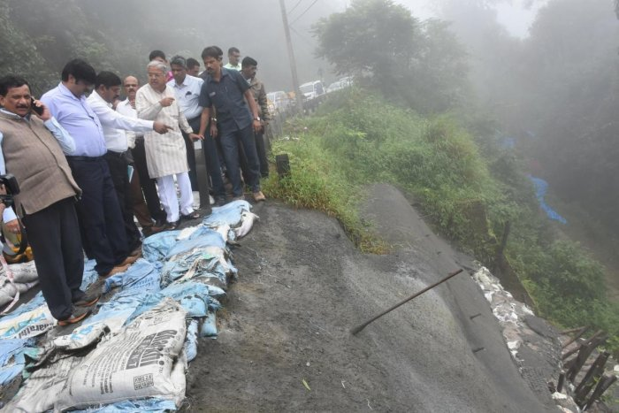 Deputy Chief Minister Govind M Karjol inspects a national highway near Madikeri, which had caved-in following rain last year.