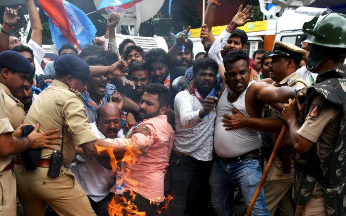 Members of the Karnataka Congress scuffle with police as they burn tyres and shout slogans against Indian Prime Minister Narendra Modi and Home Minister Amit Shah during a protest staged by the party in Bangalore. (AFP Photo)