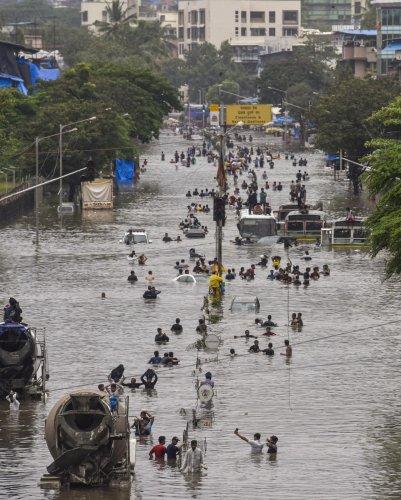People wade through a flooded railway tracks during heavy rain, in Mumbai. (PTI Photo)