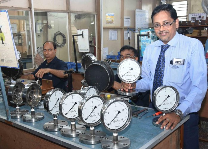 V Suresh Babu, head of Taiwac company, with the pressure guages assembled by the staff. (DH Photo)