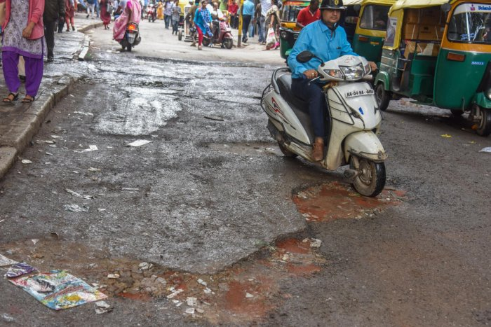 Potholes seen on Avenue Road in Bengaluru on Thursday. (DH Photo by S K Dinesh)