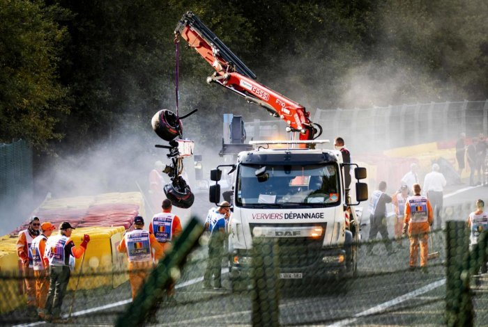 Track marshals look on as a crane lift parts of the damaged car of Sauber's Ecuadorian driver Juan Manuel Correa onto a truck following a serious accident involving several drivers during a Formula 2 race at the Spa-Francorchamps circuit in Spa, Belgium,