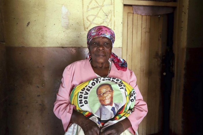 A woman holds cloth featuring portraits of former Zimbabwean President Robert Mugabe in Harare. (PTI Photo)
