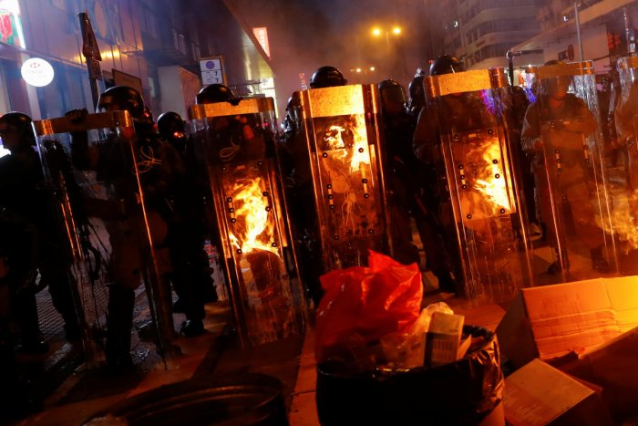 Riot police officers stand behind a burning barricade during a demonstration in Mong Kok district in Hong Kong. (Reuters Photo)