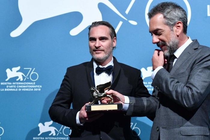 "US director Todd Phillips (R) and US actor Joaquin Phoenix, hold the Golden Lion award for Best Film that Philipps received for the movie ""Joker"" during the awards ceremony winners photocall of the 76th Venice Film Festival on September 7, 2019 at Venice"