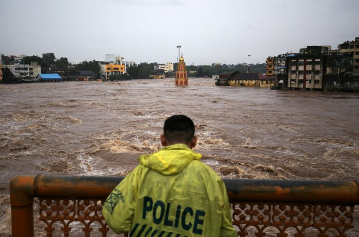 A policeman stands on a bridge as temples and houses are seen submerged in the waters of overflowing river Godavari after heavy rainfall in Nashik (Reuters Photo)