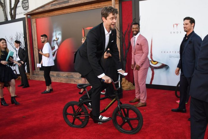 """Andy Muschietti rides a bicycle on the red carpet during the World premiere of """"It Chapter Two"""" at the Regency Village theatre in Westwood, California. (Photo by AFP)"""
