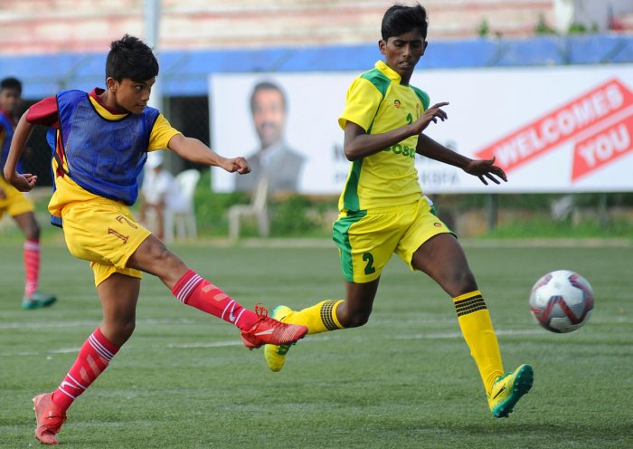 Pondicherry player Anandhu Krishna PV (left) scores his third goal against as Pitla Saiyashwanth of Telangana tries to defend during the National Sub Junior Championship NFC, South zone qualifying football tournament, at KSFA, in Bengaluru on Sunday. | DH