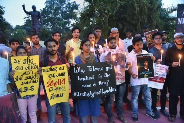 People take out a candle light march as they hold placards to protest against the death of 24-year-old Tabrez Ansari due to mob lynching, in Patna. (Photo/PTI))