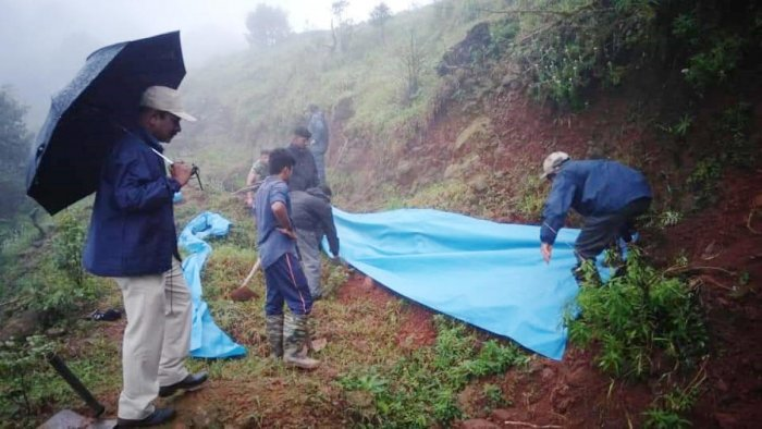 The place, where a hill developed cracks in Brahmagiri, was covered withplastic sheets, as a precaution.