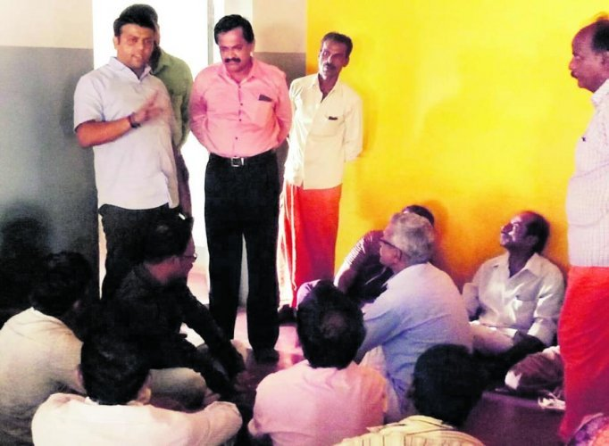 Belthangady MLA Harish Poonja is seen addressing parents staging a protest at the day care centre for endosulfan victims at Kokkada in Beltangady taluk on Saturday. (DH Photo)