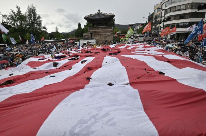 South Korean protesters tear a huge Japanese rising sun flag during an anti-Japanese rally marking the anniversary of Korea's liberation from Japan's. AFP Photo