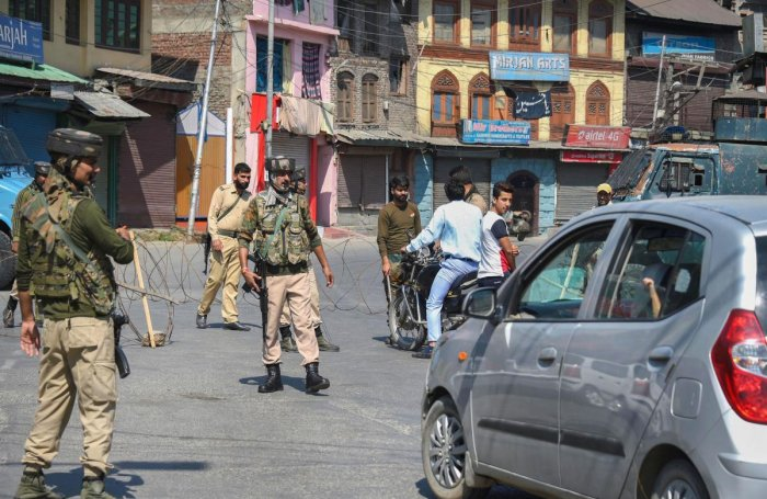 Security personnel divert traffic during curfew like restrictions in Srinagar (PTI Photo)