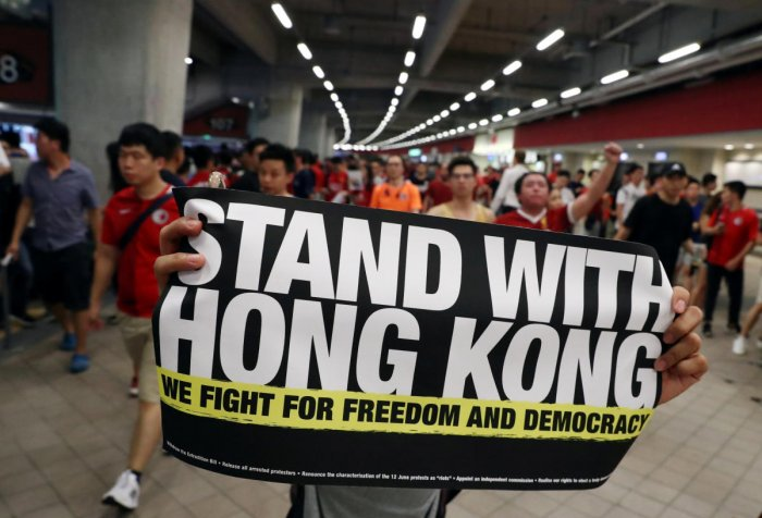 A demonstrator holds a sign in support of anti-government protesters at a football World Cup qualifier match between Hong Kong and Iran, at Hong Kong Stadium. Reuters Photo