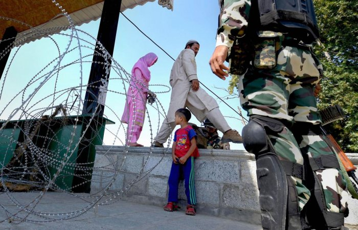 A couple makes way by a barricade of razor wires during curfew-like restrictions in Srinagar, Tuesday, Sept. 10, 2019. (PTI Photo)