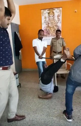 A video grab shows PSI Srikante Gowda (left) thrashingaccused Yeshwanth (inset) with his lathi, even as two constables pin him to the ground.