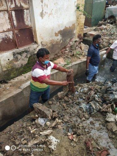 Volunteers clean up a drainage in Holealuru, Gadag