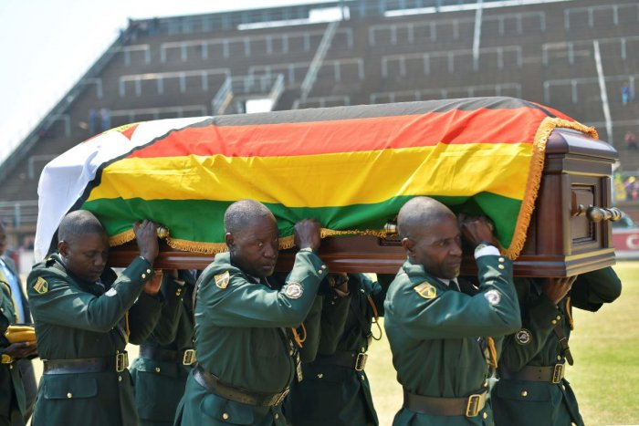 Soldiers in ceremonial uniform carry the casket of Zimbabwe's former President, the late Robert Mugabe after it arrived at Rufaro stadium. (AFP Photo)