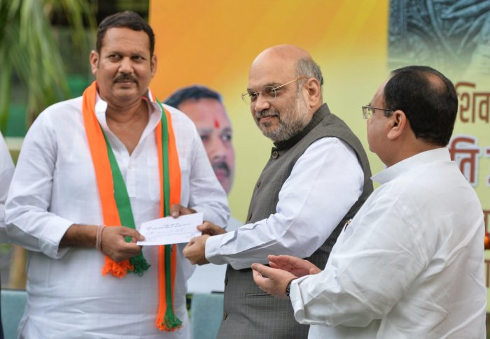 Home Minister Amit Shah gives party membership slip to senior NCP leader Udayanraje Bhosale, after the latter joined BJP. PTI file photo