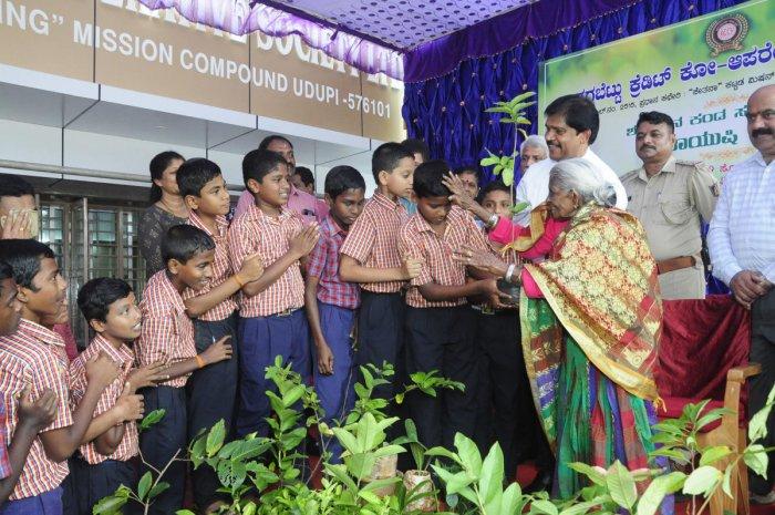 Environmentalist Saalumarada Thimmakka blesses children before handing over saplings to them at Christian School at Badagubettu in Udupi.