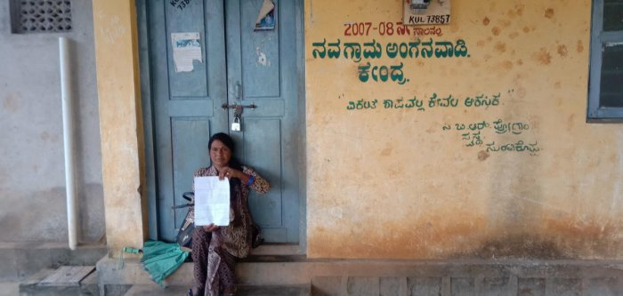 Anganwadi assistant K A Shantha stages a protest in front of Navagrama Anganwadi Centre in Kushalnagar, alleging harassment by teacher Kalavathi.