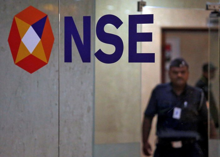 A security guard walks past the logo of the National Stock Exchange (NSE) inside its building in Mumbai. (Reuters Photo)