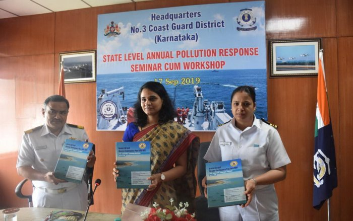 Deputy Commissioner Sindhu B Rupesh (centre) and Coast Guard Commander S S Dasila (left) release a book during a state-level annual pollution response seminar-cum-workshop organised at Coast Guard headquarters in Panambur on Tuesday.