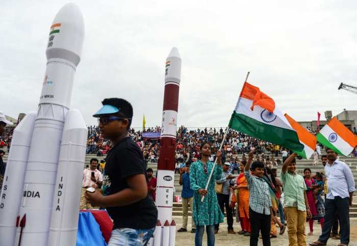 Students wave Indian national flags as the Indian Space Research Organisation's (ISRO) Chandrayaan-2 (Moon Chariot 2), with on board the Geosynchronous Satellite Launch Vehicle (GSLV-mark III-M1), has been launched in Sriharikota in the state of Andhra Pradesh on July 22, 2019. Photo credit: AFP