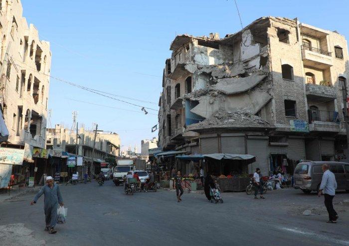 People walk near heavily damaged buildings in the rebel-held city of Idlib in northwestern Syria. (AFP Photo)