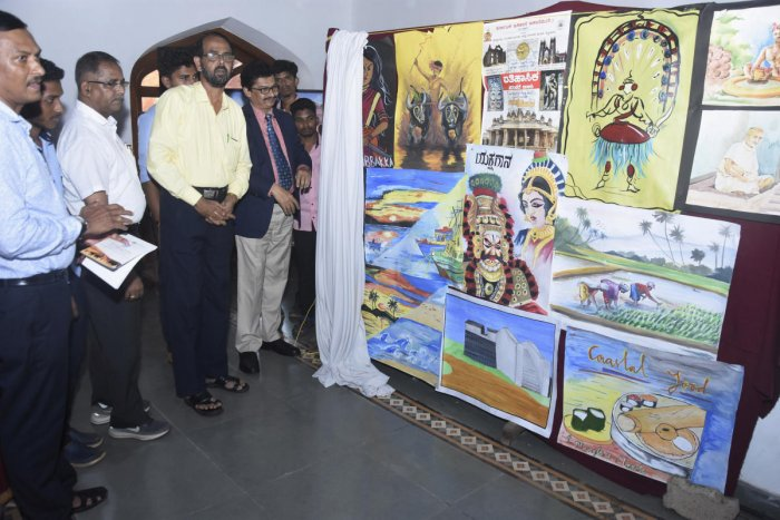 Mangalore University Vice Chancellor Prof P S Yadapadithaya unveils paintings by the students of University College, Mangaluru, during a seminar on Wednesday.