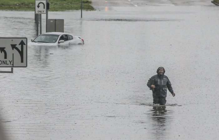 A man walks through the flooded feeder roads off of highway 69 North on September 19, 2019 in Houston, Texas. (Photo by AFP)