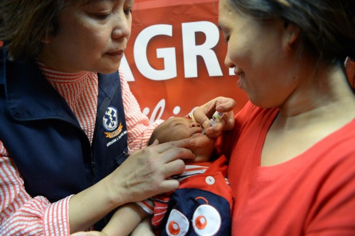 mother watches as a health worker administers a polio vaccine during an anti-polio campaign in Manila. (AFP Photo)