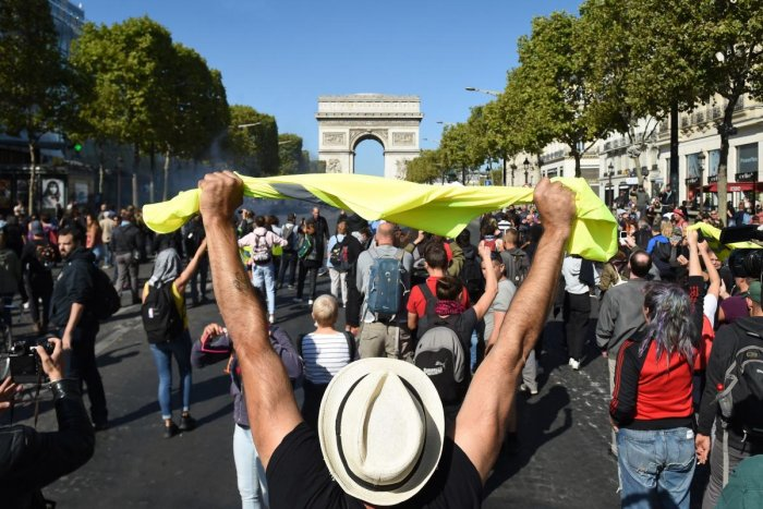 """A man holds up a yellow vest in front of the Arc de Triomphe on the Champs Elysees avenue during an anti-government demonstration called by the """"yellow vest"""" (gilets jaunes) movement, on September 21, 2019 in Paris. AFP"""