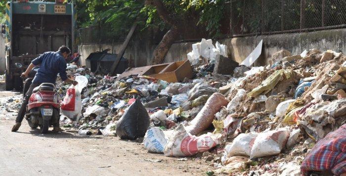 A man dropping of garbage near St Xavier School premises at Shivajinagar in Bengaluru on Thursday, September, 2019. Photo by B K Janardhan