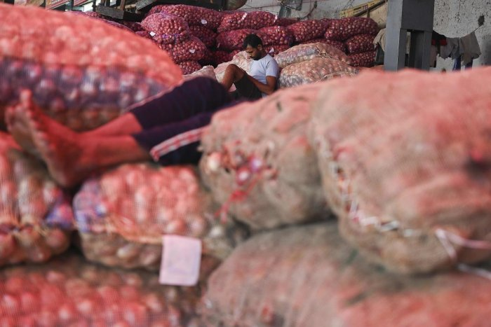 A worker sits on gunny bags filled with onions at a wholesale vegetable market in New Delhi on September 25, 2019. (AFP)