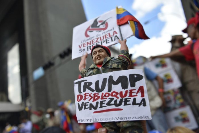 A supporter of Venezuela President Nicolas Maduro holds a figurine of late leader Hugo Chavez during a demonstration against the sanctions imposed by the US President Donald Trump, in the surroundings of Miraflores Presidential Palace in Caracas. (AFP Pho