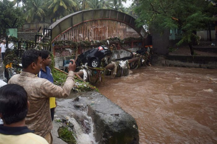 Onlookers and residents take photos of a car washed away by flash floods following heavy overnight rains in Pune on September 26, 2019. (AFP)