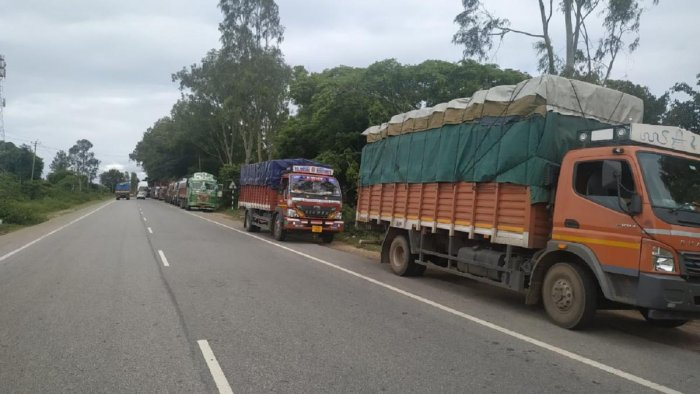 Trucks bound for Kerala lined up on the road near Madduru checkpost, Gundlupet taluk of Chamarajanagar district on Thursday.