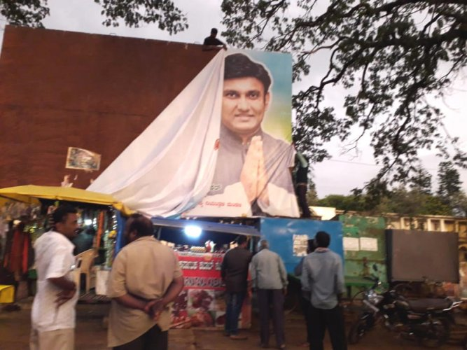 City Municipal Council staff pull down a disqualified MLA Dr K Sudhakar's poster on BB Road in Chikkaballapur on Saturday. DH Photo